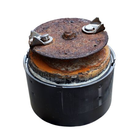 Shining stainless steel swiveling impellers mounted on top of deeply rusted metal plate above electric motor of in sink erator