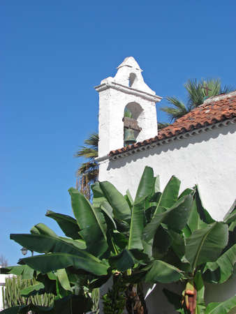 A white chapel with a belfry and a banana tree