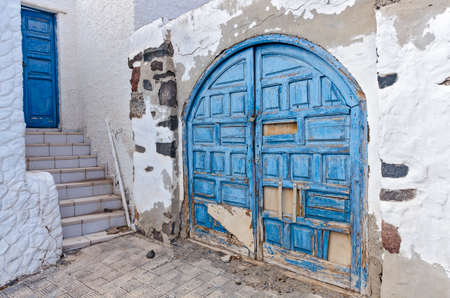 Blue door and a blue old ruined gate in a white painted house  - a typical Mediterranean Greek style architecture