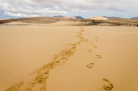 Footprints on the sandy beach of Sotavento, Fuerteventura, Canary Islands with a mountain range and stormy sky