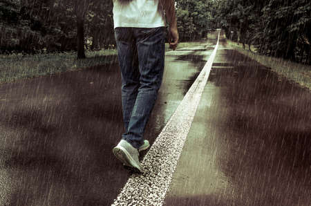 A man in jeans and sport shoes walking alone in the rain