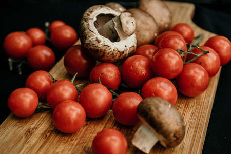 Champignons mushrooms and cherry tomatoes on a wooden background, flat lay, top view 免版税图像