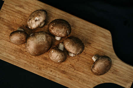 Champignons mushrooms on wooden board on black background, flat lay, top view