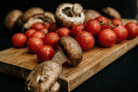 Champignons mushrooms and cherry tomatoes on a wooden background, flat lay, top view