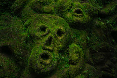 Beautiful carving faces with growing moss in Bali