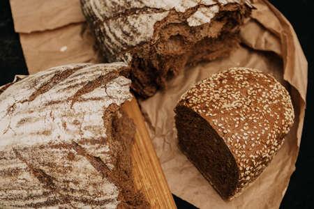 Fresh bread on paper on wooden background Foto de archivo