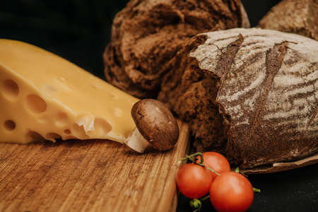 Champignons mushrooms, cherry tomatoes bread and cheese on black background, flat lay, top view 免版税图像