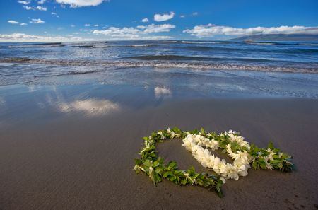 leis: Heart shaped flower lei and leaf garland (wedding leis) on a tropical beach