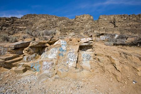 defaced: Graffiti on desert mountains (Eastern Washington) under blue sky