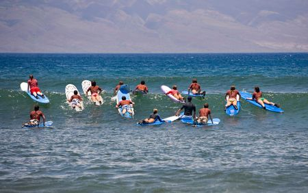 headed: Surf school - several surfboarding students headed into an ocean swell