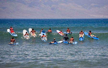 Surf school - verschillende surfboarding studenten onder leiding in een oceaan deining Stockfoto - 3561884