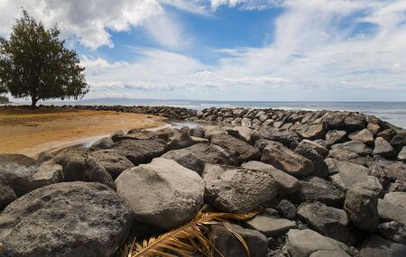 Tropical scene of a rock jetty enclosing a small lagoon by the ocean. Large tree in the background, wispy clouds and blue sky above, palm frond on the rocks in foreground.