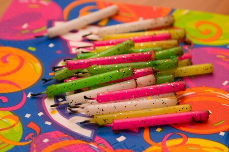 Approximately 21 fluorescent colored used birthday candles, piled on brightly colored napkin.