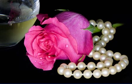 dewey: A bright pink rose with dewey petals lays next to string of pearls and a glass of white wine, on a black background Stock Photo