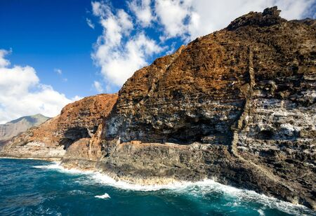 Rugged volcanic cliffs of Kauais remote Na Pali coastline, framed by blue sky and azure water,  cliffs show caves and unusual geological formations.