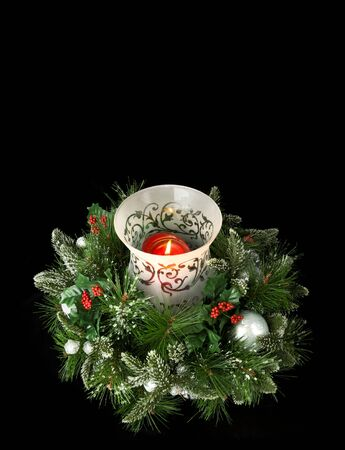 Christmas table centerpiece with hurrican glass, glowing candle and frosted greenery, isolated on black, lots of room for copy photo