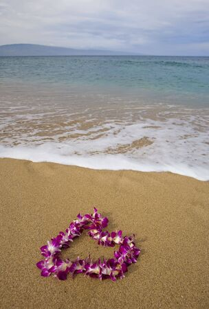 maui: Purple orchid flower lei on a golden sandy tropical beach with island on distant horizon