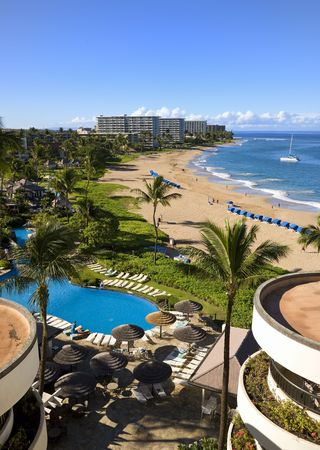 View of a long tropical beach from above (Kaanapali, Maui). Interesting round buildings in foreground.