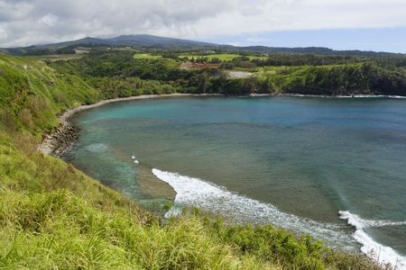 Horseshoe shaped Honolua Bay on Maui, Hawaii shows beautiful azure water and coral reef underneath