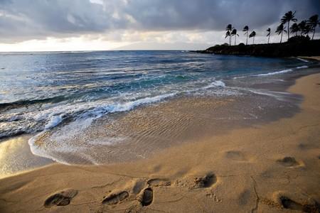 Beautiful idyllic tropical beach at sunset casts shadows into deep footprints