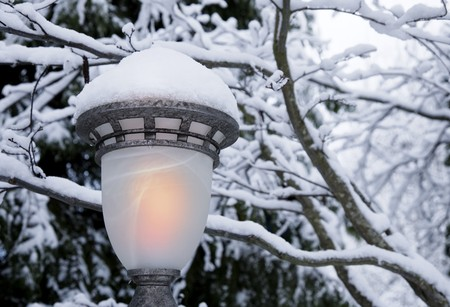 Snowy scene with closeup on glowing lamplight