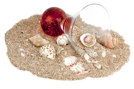 Sand in small patch, seashells and a decorative cocktail glass, isolated on white