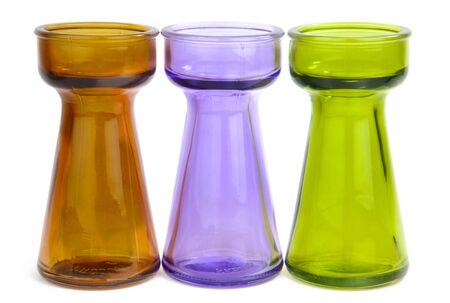 Three small clear colored glass vases isolated on white