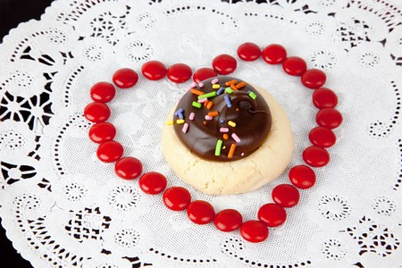 Red candies arranged in the shape of a heart, surround a delicious cookie with multicolored sprinkles on white doily