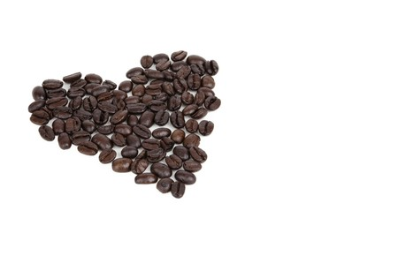 Whole coffee beans arranged in the shape of a heart, isolated on white background, lots of room for copy