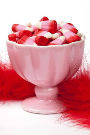Pink candy corn in pink candy dish with red feather boa on a white background Stock Photo