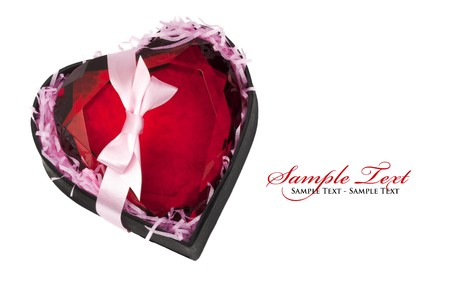 Red crystal heart-shaped paperweight inside a black gift box, tied with a pink bow and isolated on white, with sample text in copy space
