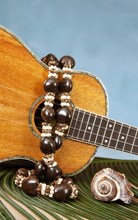 Closeup of beautiful Hawaiian koa wood ukulele with abalone inlay, on a palm frond draped with kukuinut lei, and a seashell on blue backgound