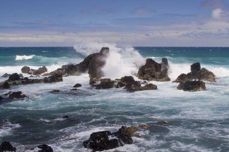 Giant wave splashes large volcanic rocks on tropical shore