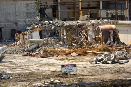Concrete rubble and crumpled machinery in demolished industrial plant, sign in foreground says