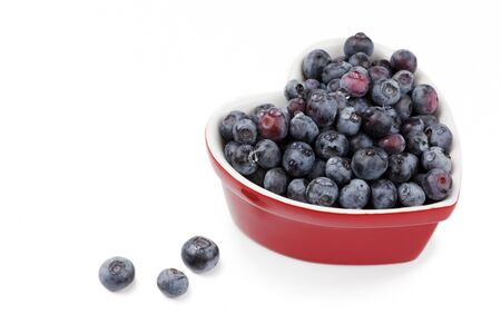 Fresh washed blueberries in a a red heart shaped bowl, isolated on white Stock Photo