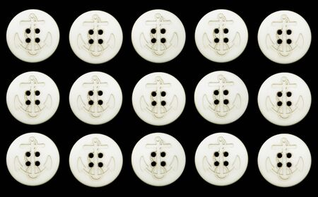 15 ivory colored vintage navy buttons with rope and anchor motif, each with 4 holes, isolated on a black background, with path.