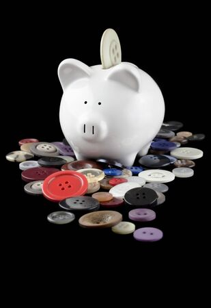 Small ceramic piggy bank sitting in a pile of old buttons, with one going into the slot on the pig, isolated on black