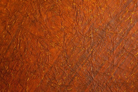 Background of crushed deep reddish brown paper with tiny flecks of gold Stock Photo
