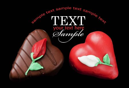 Romantic chocolate and red heart shaped petits fours (small cakes) on a field of black with sample text Stock Photo