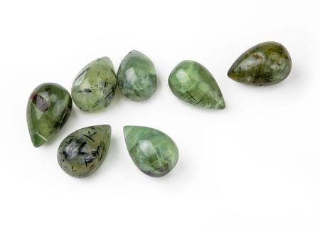 Seven green garnet teardrop-shaped gemstones, isolated on white background
