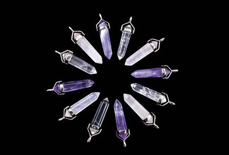 Twelve crystal quartz, rose quartz, and amethyst points with silver mountings arranged to create a circular sunburst, isolated on black background