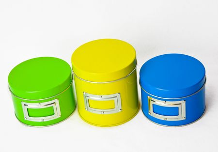 Green, yellow and blue round metal cans with silver trim isolated on white background.