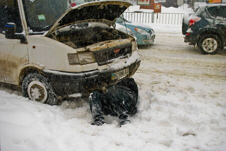 The driver of the car repairs lying in the snow Lviv Ukraine 15 03 2013