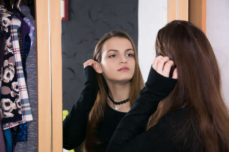 The girl at the mirror does makeup and hairstyle. The girl chooses an image.
