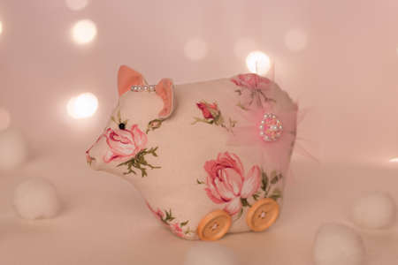 Handmade pink piglet with a brooch on the hip stands on the background of Christmas lights and balls