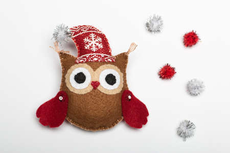 two brown felt owls in handmade hat with a Christmas hat