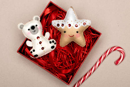 handmade star and bear of felt in a gift box with red tinsel