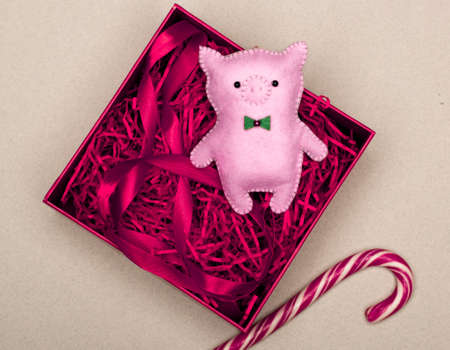 handmade pink pig in a gift box with red tinsel