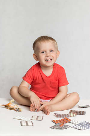 A happy baby Toddler in a live coral color T-shirt sits among the pills and drugs. A photograph to illustrate articles about childhood diseases and vaccines.