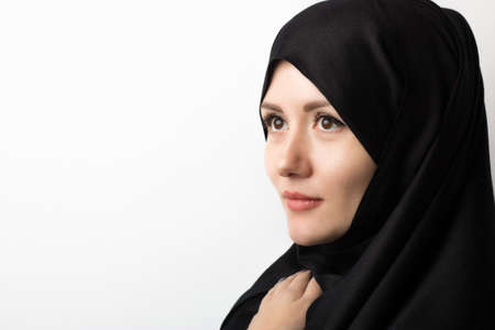 portrait of a beautiful muslim girl in hijab on a white background in the studio, with space for text. Concept for articles about Islam and the place of women in the family and religion.